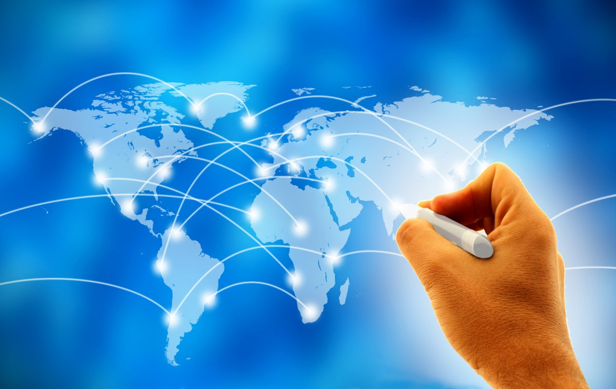 Business man drawing network on world map